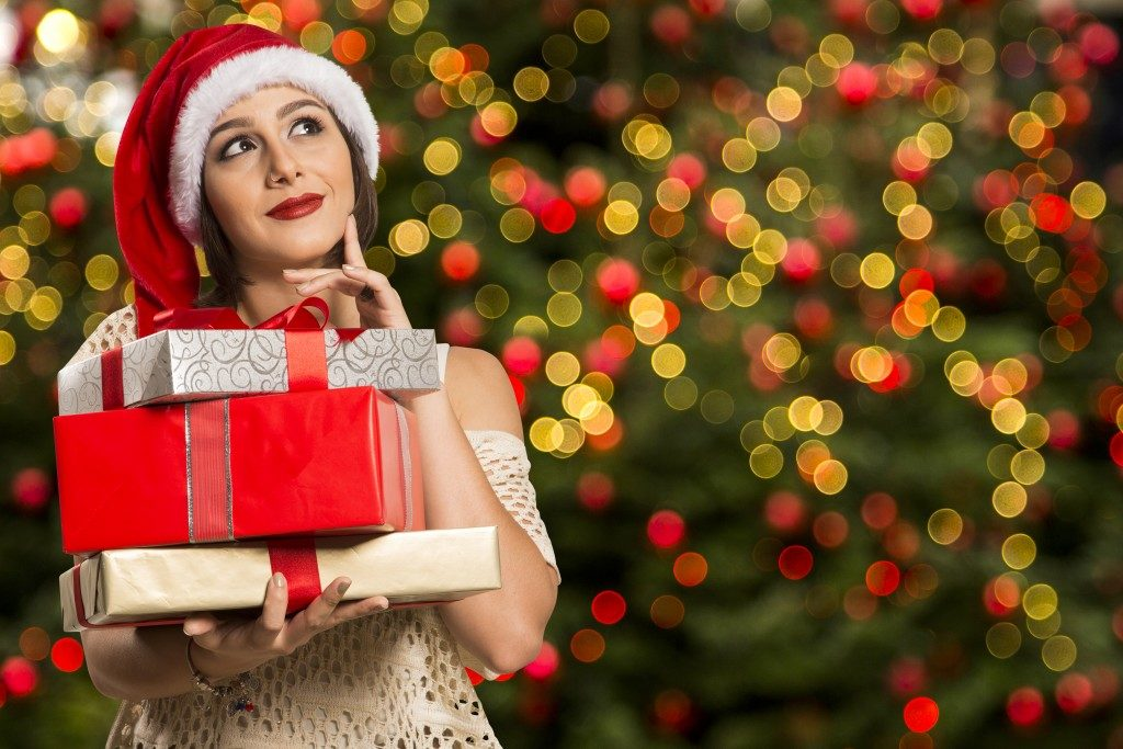 Woman in santa hat holding gifts