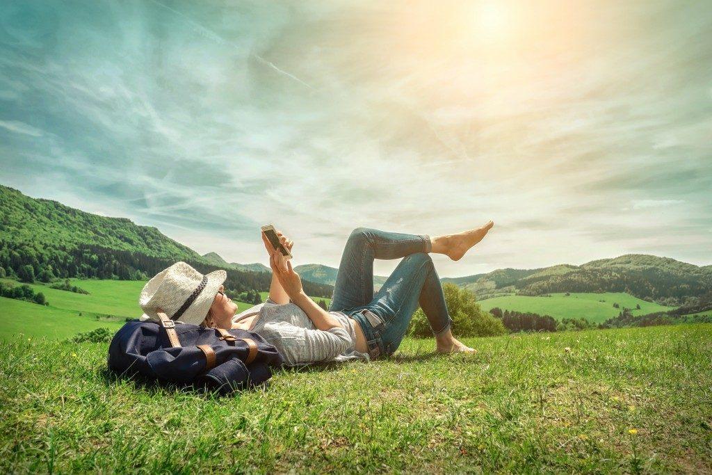 woman lying on grass holding phone