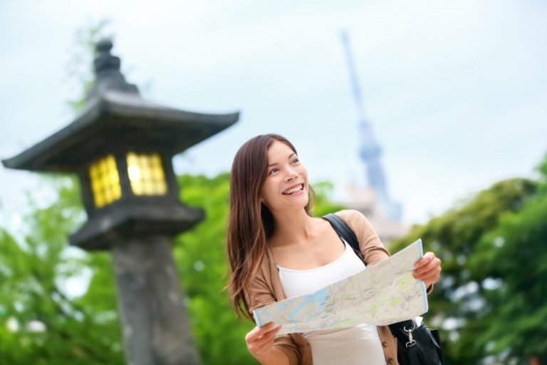 smiling tourist woman holding map